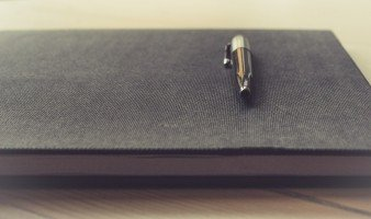 ball-pen-on-top-of-elegant-notebook